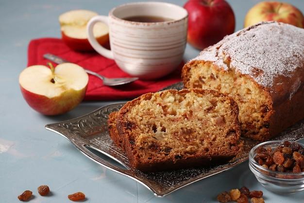 Bolinho caseiro com semolina, maçãs e passas em uma bandeja de metal em um azul claro e uma xícara de café
