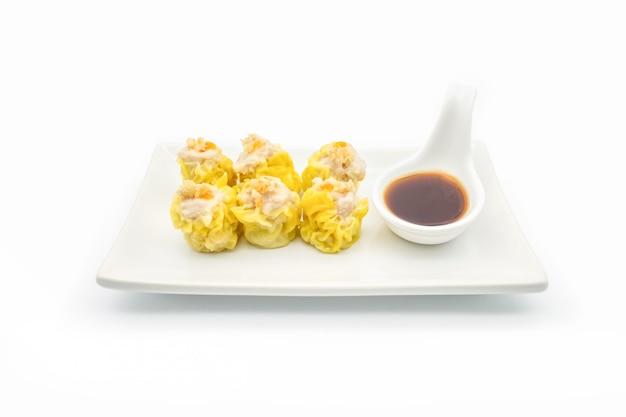 Bolinho chinês cozido no vapor na placa branca isolar no fundo branco
