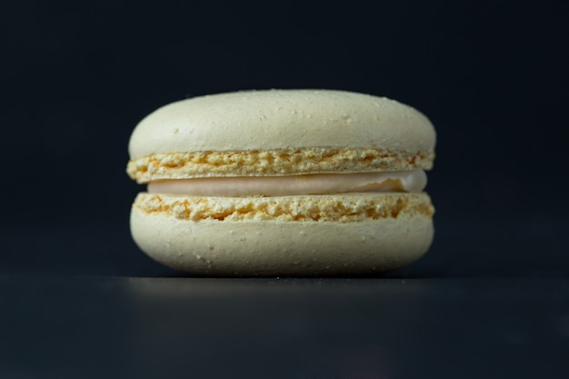 Bolinho de amêndoa no fundo escuro, macarons franceses bege das cookies.