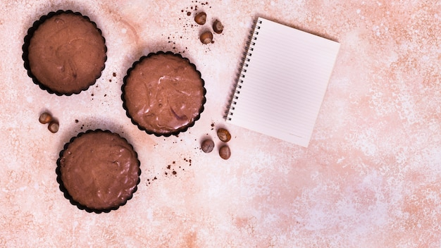 Bolinho de chocolate; bloco de notas de avelã e espiral no plano de fundo texturizado