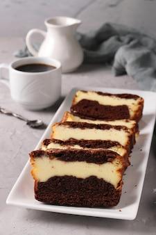 Bolinho de chocolate caseiro fatiado com queijo cottage localizado em um prato branco sobre cinza