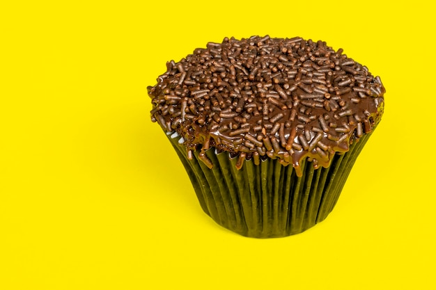 Bolinho de chocolate com granulado, com fundo amarelo