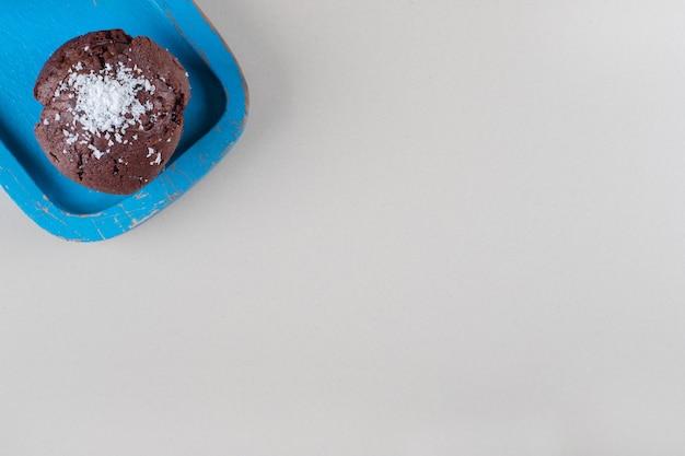 Bolinho de chocolate em uma bandeja azul sobre fundo de mármore.