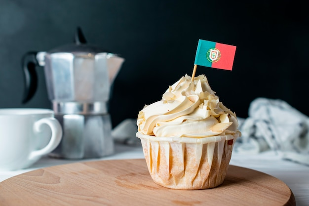 Bolinho de creme de amêndoa recém-assado e migalhas de amêndoa com bandeira de portugal para o chá da manhã