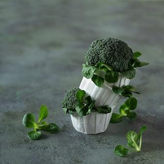 Bolinho de dieta de brócolis e salada de milho sobre fundo verde