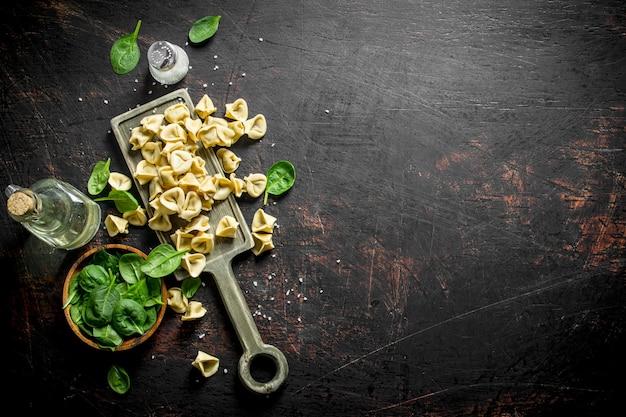 Bolinho de massa cru com carne e folhas de espinafre em uma tigela