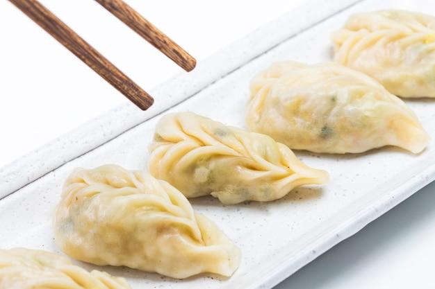 Bolinho de massa fervido e fresco na placa. comida chinesa com vapores quentes no fundo.