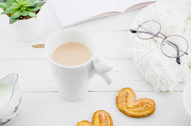 Bolinho de massa folhada palmiers com xícara de chá branco de porcelana na mesa de madeira
