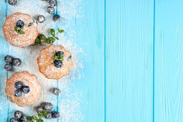 Bolinho de mirtilo. queque cozido caseiro com mirtilos, bagas frescas, hortelã, açúcar de confeiteiro sobre fundo azul de madeira.
