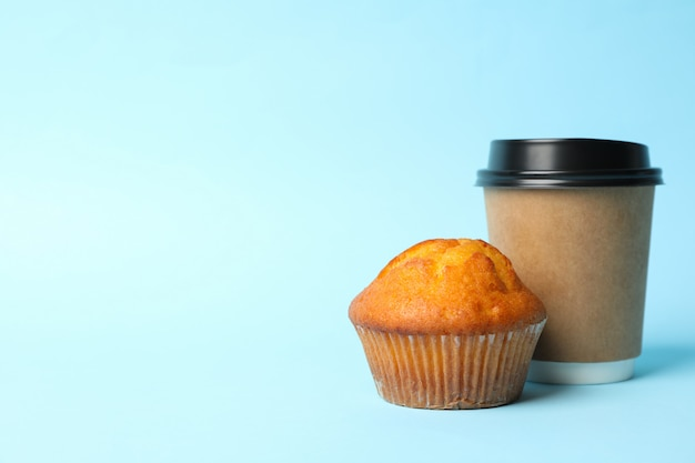 Bolinho de papel e chocolate muffin sobre fundo azul, espaço para texto