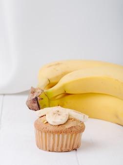 Bolinho de vista de ângulo frontal com bananas em uma superfície branca