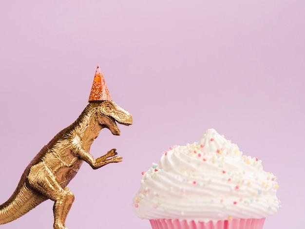 Bolinho delicioso e dinossauro com chapéu de aniversário