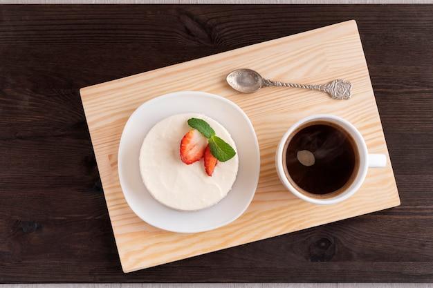 Bolinho e café na bandeja de madeira.
