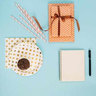 Bolinho e palhas perto de presente e bloco de notas