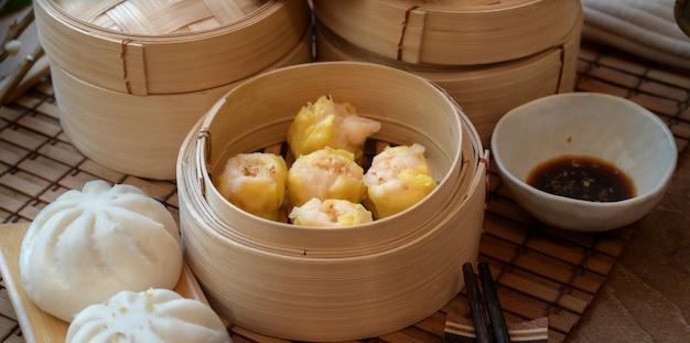 Bolinho no vapor chinês e pão de porco cozido no vapor em um vaporizador de bambu com pauzinho