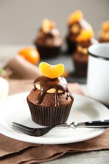 Bolinho saboroso com fatia de tangerina e chocolate em um prato sobre superfície de madeira clara
