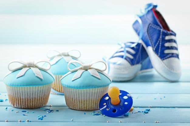 Bolinho saboroso com laço e sapatos de bebê na cor de fundo de madeira