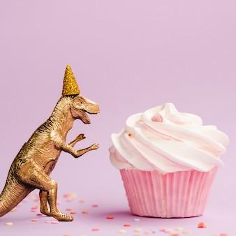 Bolinho saboroso e dinossauro com chapéu de aniversário