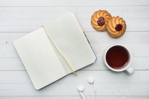 Bolinhos aéreos da vista, caderno e uma chávena de café. copie o espaço. vista plana leiga