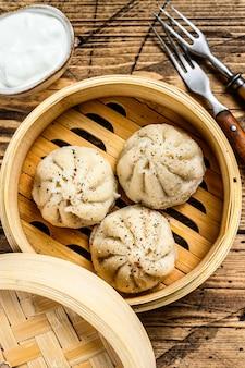 Bolinhos asiáticos cozidos no vapor manti em um vaporizador de bambu