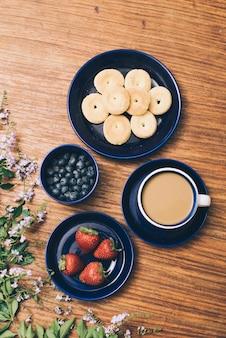 Bolinhos assados; xícara de café; mirtilo e morango com flores rosa em fundo de madeira