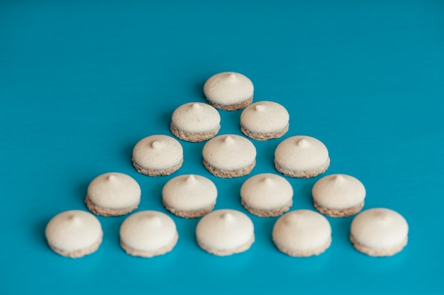 Bolinhos brancos pequenos são organizados na forma de um triângulo em azul