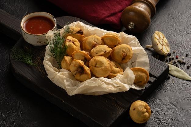 Bolinhos caseiros assados com carne, endro, ketchup, alho e folha de louro perto de um pimenteiro e guardanapo em uma mesa preta.