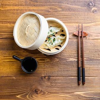 Bolinhos chineses em vapor de madeira com pauzinhos