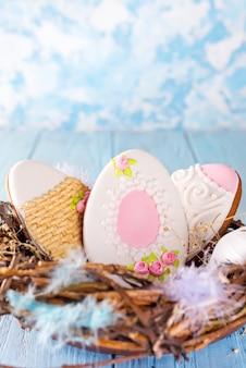 Bolinhos coloridos dos ovos de easter no ninho de madeira no fundo de madeira azul