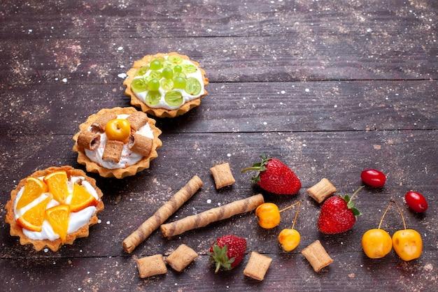 Bolinhos cremosos com uvas fatiadas, laranjas e morangos em uma mesa de madeira marrom