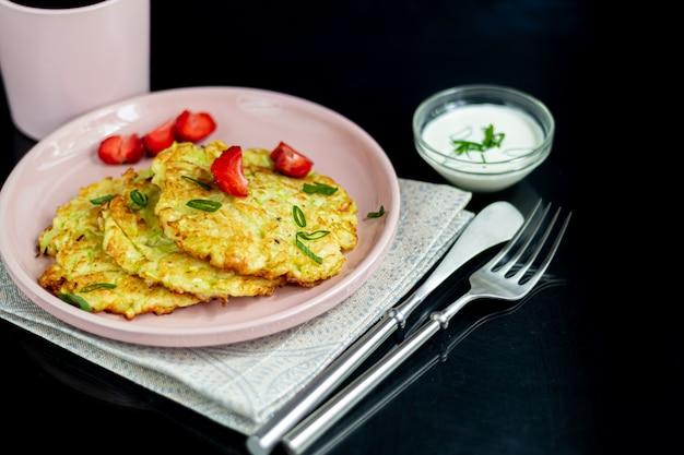 Bolinhos de abobrinha, bolinhos de abobrinha vegetariana, servidos com ervas frescas e creme de leite. decorado com morangos e cebolinha. em uma mesa escura.