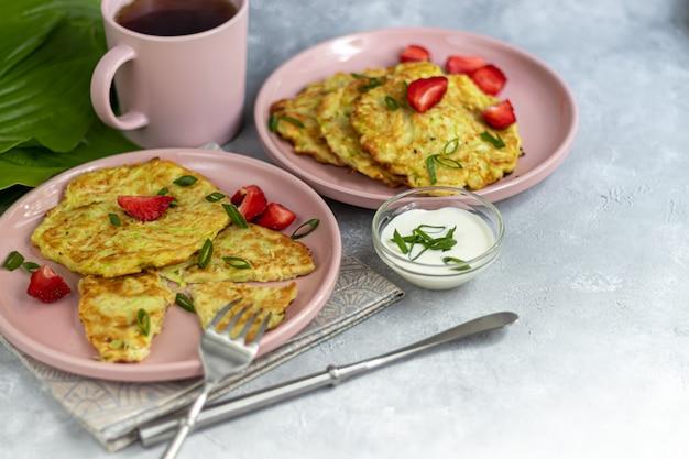 Bolinhos de abobrinha, bolinhos de abobrinha vegetariana, servidos com ervas frescas e creme de leite.