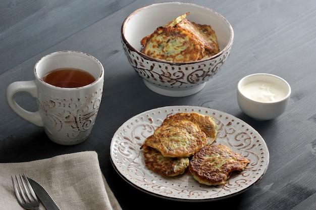 Bolinhos de abobrinha com endro em um prato fundo, chá, creme de leite