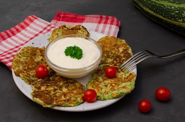 Bolinhos de abobrinha de legumes servidos com iogurte e salsa. ingredientes para cozinhar na mesa. nutrição saudável. foco seletivo.