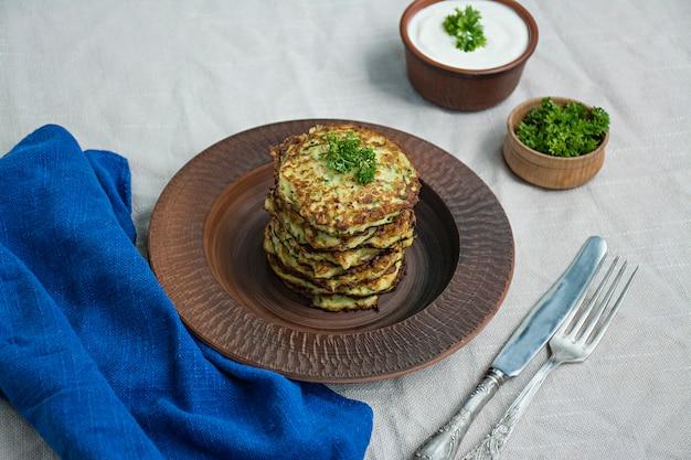 Bolinhos de abobrinha, panquecas vegetarianas de abobrinha, servidas com ervas frescas e creme de leite