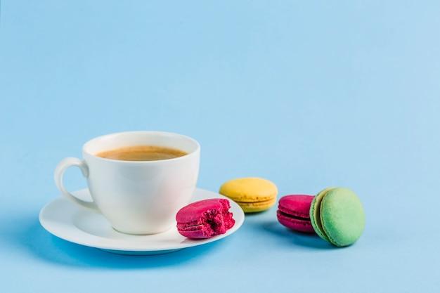 Bolinhos de amêndoa coloridos com uma xícara de café branca em um copyspace azul, close-up, flatley com copyspace