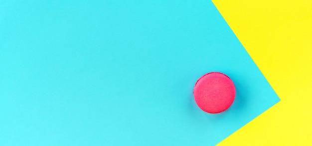 Bolinhos de amêndoa cor-de-rosa em um fundo amarelo e azul.
