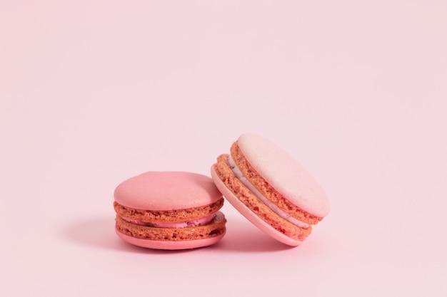 Bolinhos de amêndoa ou macaron francês doce e colorido no fundo cor-de-rosa, sobremesa.