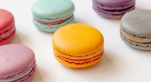 Bolinhos de amêndoa saborosos na tabela, fundo branco. fechar-se. vista do topo. bolo de sobremesa francesa macaron ou biscoito.