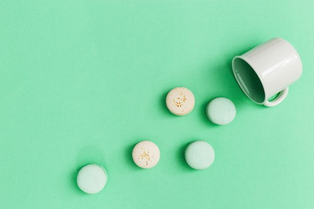 Bolinhos de amêndoa sortidos derramados fora do copo na mesa. biscoitos desintegrados na tendência cor de fundo de menta. recusa doce, ingestão excessiva de açúcar.