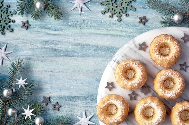 Bolinhos de anel mini bundt com açúcar de confeiteiro sobre fundo claro com galhos de pinheiro, bagas e bastões de doces