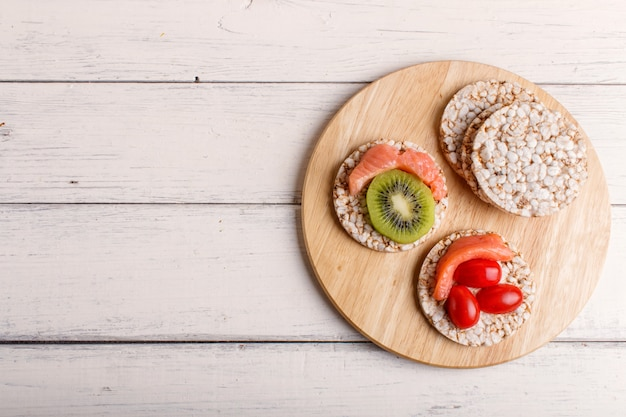 Bolinhos de arroz com salmão, kiwi e tomate cereja em madeira branca