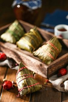 Bolinhos de arroz do festival duanwu e vinho de arroz em um prato de madeira
