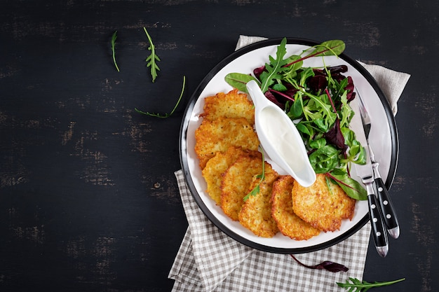 Bolinhos de batata / draniki / panquecas servido com creme azedo.