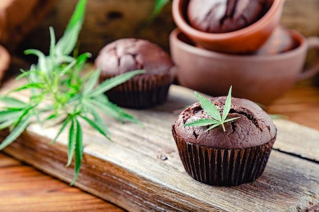 Bolinhos de bolinho de chocolate com folhas de cannabis, erva daninha cbd. drogas de maconha medicinal em sobremesa de comida. cozinhar bolos de erva daninha de chocolate de cozimento. cupcake com maconha na mesa de madeira marrom escura.