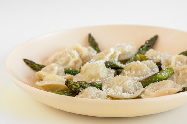 Bolinhos de carne com parmigiano e aspargos no prato bege.