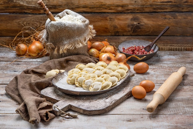 Bolinhos de carne crus - pelmeni russo na tábua