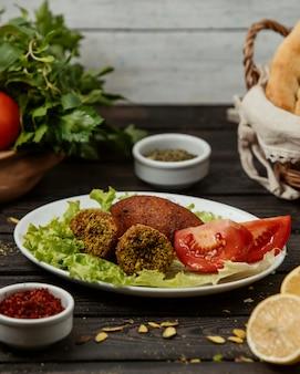 Bolinhos de carne recheados de quibe turco servidos com tomate e alface