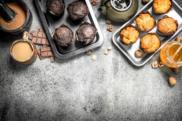 Bolinhos de chocolate e frutas na mesa rústica.