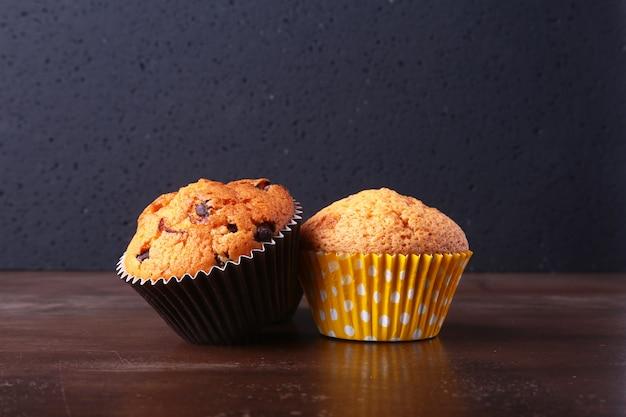 Bolinhos de chocolate saborosos, muffins em uma mesa de madeira branca
